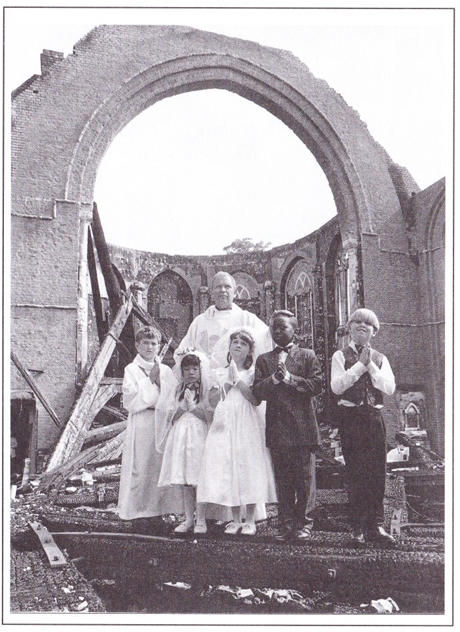 Fr Conrad Smith (Parish priest at the time) stands among the ruins with children of the parish.